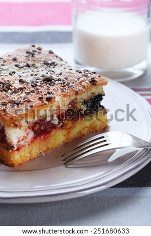 Homemade pie with jam and glass of milk on striped tablecloth background - stock photo