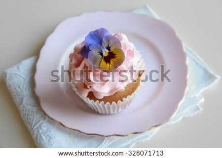 Homemade pink frosting vanilla cupcakes with edible flowers on vintage plate - stock photo