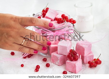 Homemade pink square marshmallows in a glass jar on white - stock photo