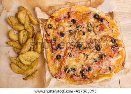 Homemade pizza with french fries on a wooden table - stock photo