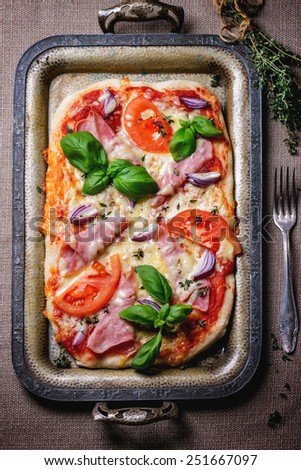 Homemade pizza with ham and tomatoes, served with fork and bundle of thyme on vintage metal tray. Top view. - stock photo