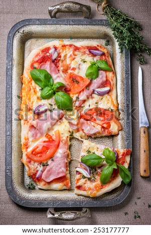 Homemade pizza with ham and tomatoes, served with knife and bundle of thyme on vintage metal tray. Top view. - stock photo
