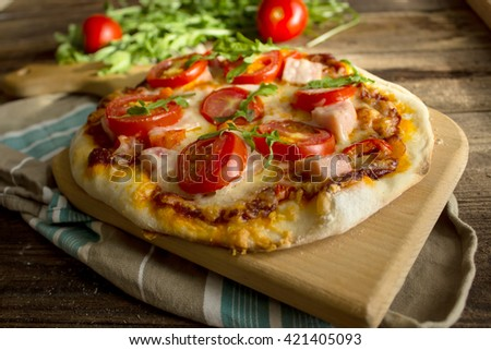 homemade pizza with ham , tomato and arugula on a wooden board. - stock photo