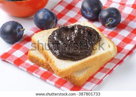 Homemade plum jam on a slice of bread - stock photo