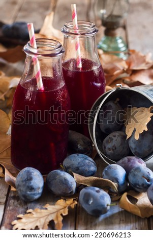 Homemade plum juice with fresh prunes and fall leaves on wooden background - stock photo