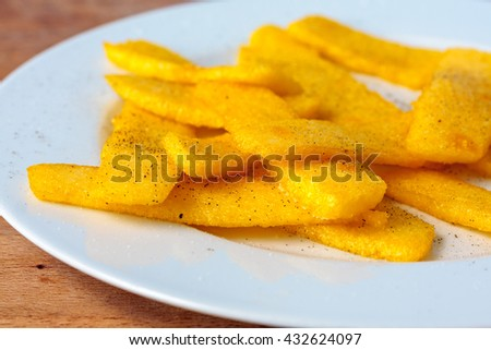 Homemade polenta chips on a white plate - stock photo