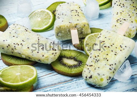 Homemade popsicles with kiwi and mint on a wooden table. Focus on the top of the frame, soft focus - stock photo