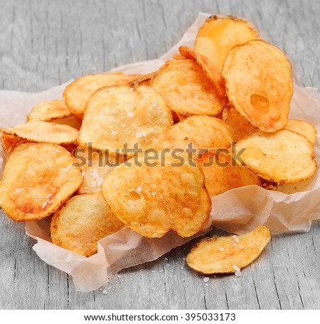 Homemade potato chips closeup on wooden texture - stock photo