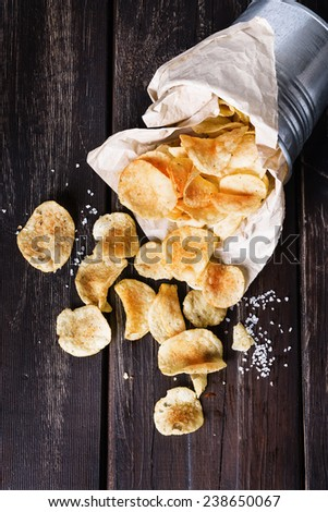 Homemade potato chips over dark wooden background. Top view; selective focus - stock photo
