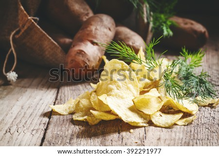 Homemade potato chips with salt and dill, raw potatoes in a bag on a old wooden dark background, selective focus - stock photo