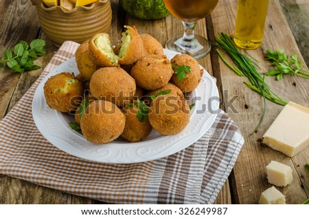 Homemade potato croquettes, original recepy with cheese and herbs, delicious czech beer behind - stock photo
