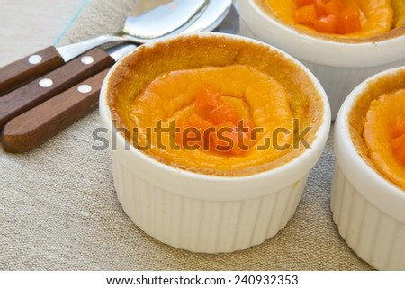Homemade pumpkin cheese cakes in white ceramic molds.Dessert spoons on a sackcloth in the background. - stock photo
