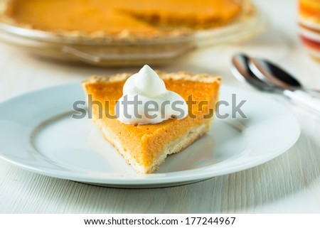 Homemade pumpkin pie with whipped cream on white plate - stock photo