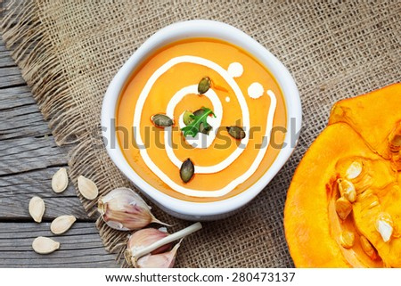 Homemade pumpkin soup with garlic and fresh cream on rustic wooden table, top view - stock photo