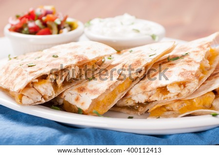 homemade quesadilla with chicken and hand made salsa plus yogurt and sour cream - stock photo