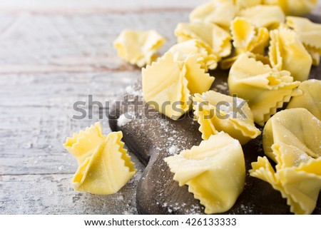 Homemade raw Italian saccottini filled with green pesto on wooden vintage cutting board. Selective focus. With copy space. - stock photo