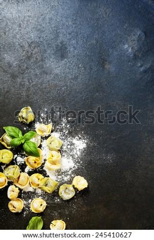 Homemade raw Italian tortellini and basil leaves on dark vintage background - stock photo