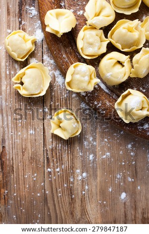 Homemade raw Italian tortellini on wooden vintage cutting board with a rolling pin. Selective focus. Food background with copy space. - stock photo