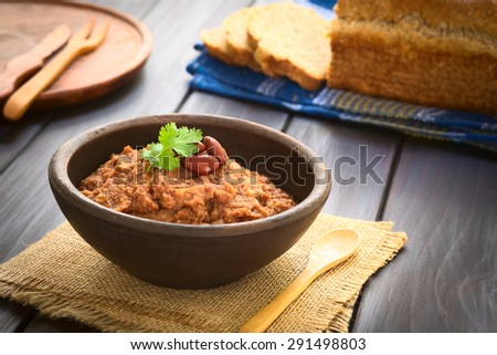 Homemade red kidney bean spread garnished with kidney beans and fresh coriander leaf in rustic bow, wholegrain bread in the back, photographed with natural light (Selective Focus, Focus on the leaf)  - stock photo