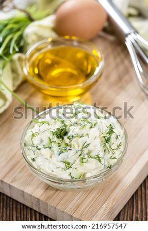 Homemade Remoulade on wooden background with fresh herbs (close-uo shot) - stock photo