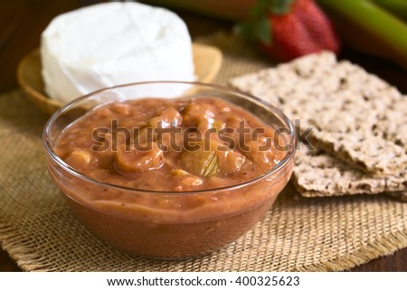 Homemade rhubarb and strawberry chutney in glass bowl, photographed with natural light (Selective Focus, Focus one third into the chutney) - stock photo