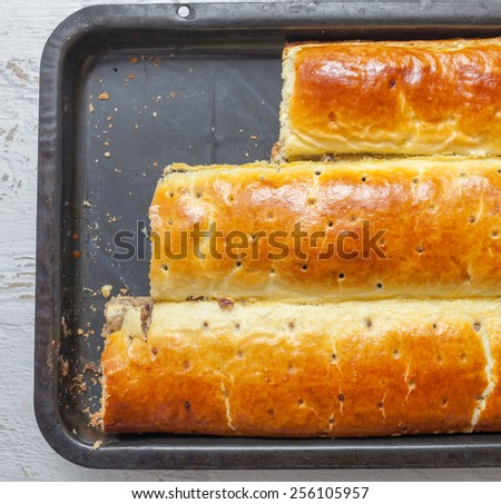 Homemade roll with poppy seeds, walnut and cheese - stock photo