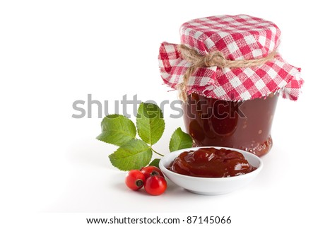 Homemade rose hip jelly in jar with fresh rose hip - stock photo
