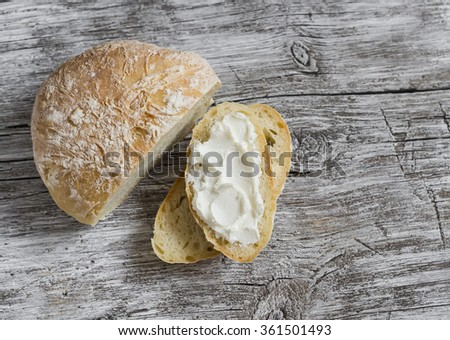 Homemade rustic bread on light wooden board - stock photo