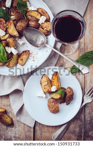 Homemade rustic dinner: a glass of wine and a baked potato with soft cheese and fresh basil in a white plate on a wooden board - stock photo