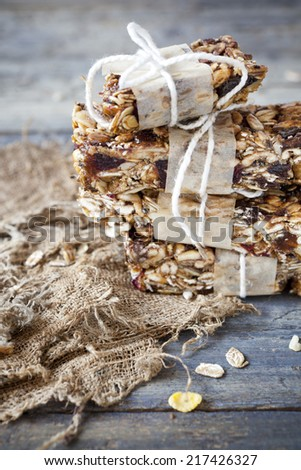 homemade rustic granola bars with dried fruits and handmade packaged on old bowl on vintage blue wooden background - stock photo
