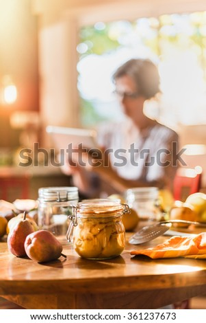 Homemade rustic jar of fruits with pears around on wooden table. The pears are canned to preserve their freshness. A woman with tablet is sitting in the kitchen in the blur background. shot with flare - stock photo