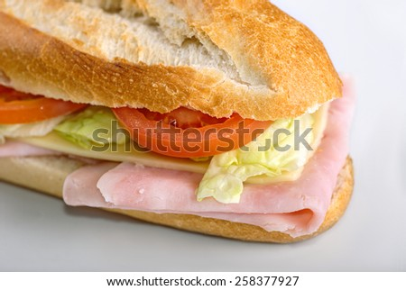 Homemade sandwich with ham, salad, cheese and tomatoes in white bread baguette - stock photo