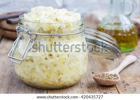 Homemade sauerkraut with cumin in a glass jar  - stock photo