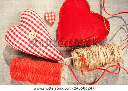 Homemade sewed couple red cotton love heart.  Indoor closeup. - stock photo