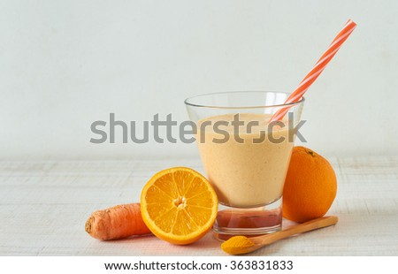 Homemade smoothie made from raw almond milk with orange, carrot and turmeric powder - stock photo