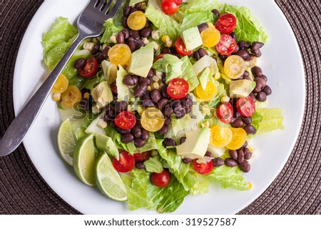 Homemade southwest black bean lime salad with corn, cherry tomatoes, lettuce, avocado, and black beans with vinaigrette dressing for clean eating - close up - stock photo