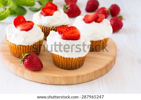 Homemade strawberry cupcakes with whipped cream topping - stock photo