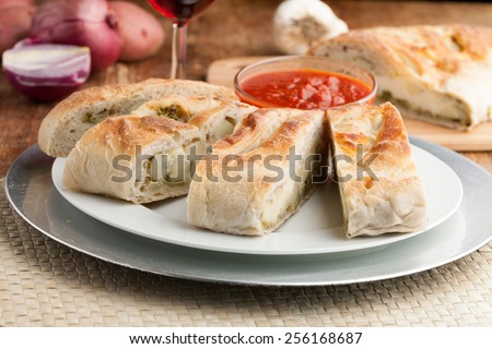Homemade stromboli or stuffed bread with broccoli potatoes garlic onions and mozzarella cheese along with a side of marinara dipping sauce. - stock photo