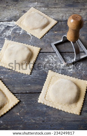 homemade stuffed ravioli big size uncooked on wooden table with flour and tool - stock photo