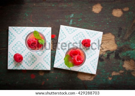 Homemade summer cold raspberry cocktail with crushed iced and alcohol in glasses on a vintage background, top view with place for text - stock photo