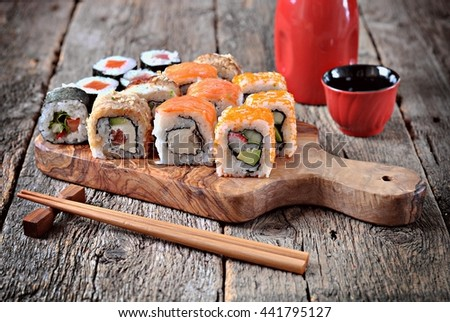 Homemade sushi with salmon, smoked eel, curd cheese and vegetables on a wooden background - stock photo