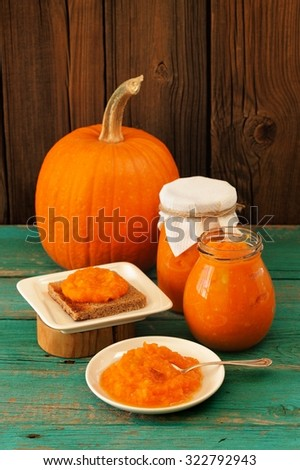 Homemade sweet pumpkin jam on rye toast, in white plate and in glass jars with whole pumpkin - stock photo