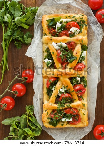 Homemade tart with cottage cheese, herbs and cherry tomatoes. Viewed from above. - stock photo