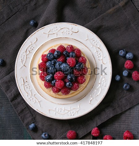 Homemade tart with custard, fresh raspberries and blueberries, served on white vintage plate on textile napkin over old wooden table. Dark rustic style. Flat lay. Square image - stock photo