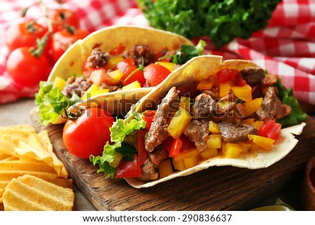 Homemade tasty burrito with vegetables and potato chips on cutting board, on wooden background - stock photo