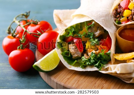 Homemade tasty burrito with vegetables, potato chips on cutting board, on wooden background - stock photo