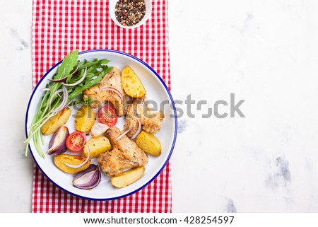 Homemade tasty roasted chicken wings with roasted potato with vegetables in an enamel bowl, top view, horizontal with place for text - stock photo