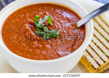 Homemade tomato and basil soup in white round bowl with spoon and grilled cheese panini sandwich - stock photo