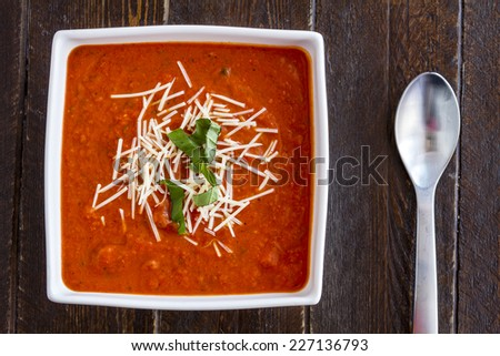 Homemade tomato and basil soup sprinkled with parmesan cheese in white square bowl and spoon - stock photo