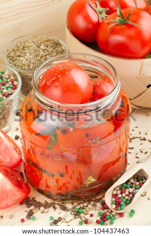 Homemade tomatoes preserves in glass jar. Canned tomatoes. - stock photo